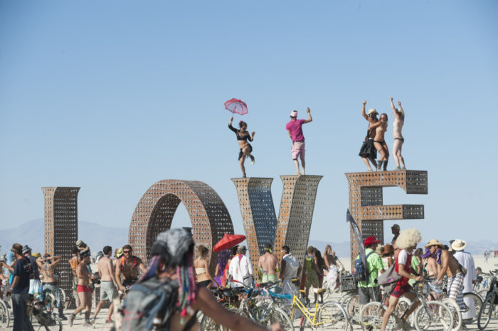 BLACK ROCK CITY, NV - SEPT 2: First-time Burner Sonja Lercer of Whistler, B.C., Canada, dances on the LOVE installation at last week's 25th annual Burning Man festival. (Photo by Keith Carlsen For the Washington Post)